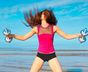 woman-holding-weights-on-a-beach